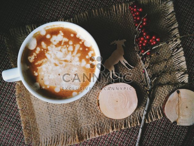 Cup of coffee and branch with red berries on sacking - Free image #136257