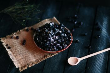Berries in the plate and wooden spoon on the table - image #136287 gratis