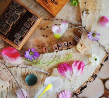 Petals and small cubes with letters on wooden background - бесплатный image #136407