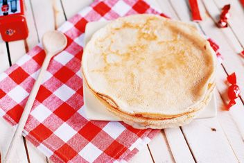 Pancakes and wooden spoon on checkered dishcloth - image #136447 gratis