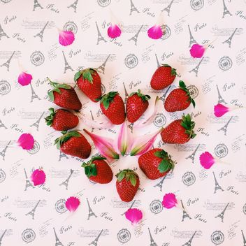 Strawberries and pink petals - image #136467 gratis