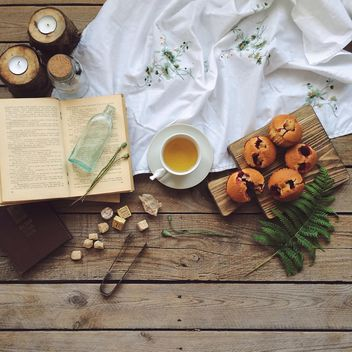 Open book, cup of tea and cupcakes - бесплатный image #136587
