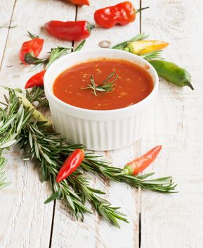 tomato sauce with rosemary and chili peppers on a wooden table - image #183367 gratis