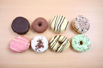 Donuts with different flavors on wooden background - Kostenloses image #187797