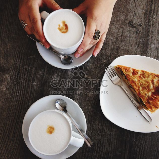 Cup of coffee in female hands and piece of pie on wooden background - Free image #198397