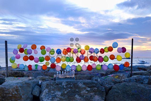 Ballons colorés sur le bord de mer sur fond de coucher de soleil - image gratuit #272317
