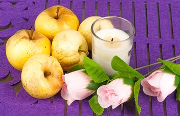 Yellow apples, roses and candle on purple background - бесплатный image #272527