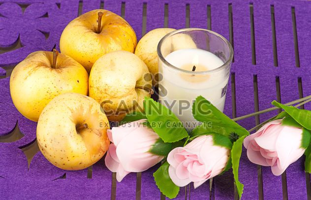 Maçãs amarelas, rosas e velas no fundo roxo - Free image #272527