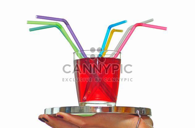 vaso de jugo con la paja en una bandeja de - image #273207 gratis