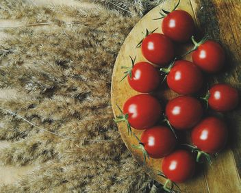 Tomatoes on wooden board on dry spicas - image #274857 gratis