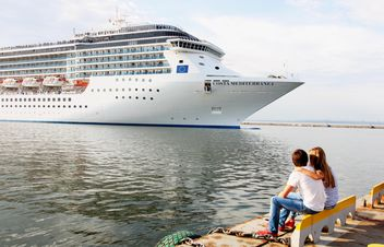 Couple looking at large cruise ship at sea - image #301597 gratis