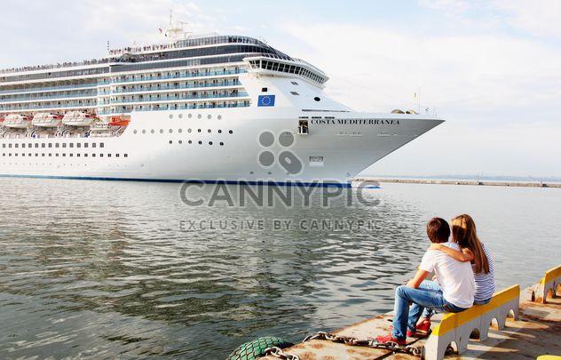Couple looking at large cruise ship at sea - Free image #301597