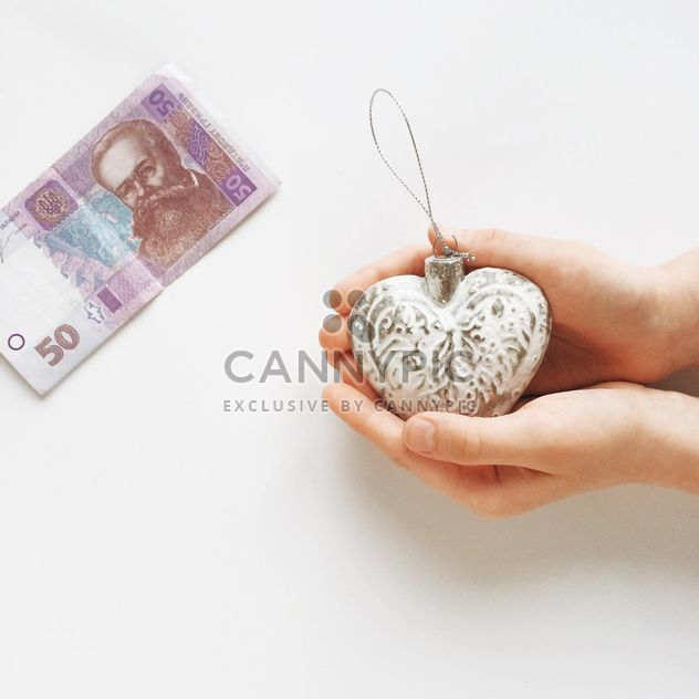 Woman's hands holding christmas toy and money on the white table - Free image #329237