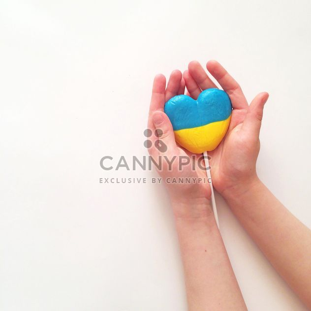 Hands holding lollipop in colors of Ukrainian flag on white background - Free image #329297