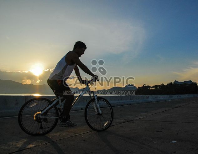 Man riding a bicycle down the road - Free image #330357