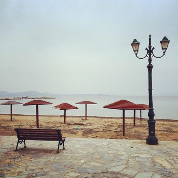 Bench, umbrellas and lantern on quay - бесплатный image #331757