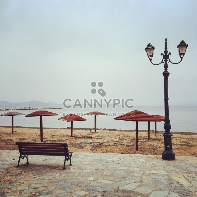 Скамейка, зонтики и фонарь на набережной - бесплатный image #331757