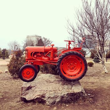 Red tractor on stone - image gratuit #332157