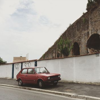 Old Fiat car parked near ancient arch - бесплатный image #332397
