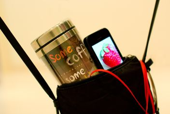 Cup of coffee and smartphone in handbag - image gratuit #337907
