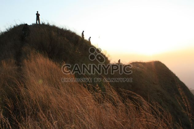 People on rock at sunset - Free image #338507