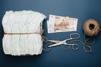 Diapers, skein of thread, scissors and money on blue background. Diapers for 3 dollars, Cheboksary, Russia - Free image #342557