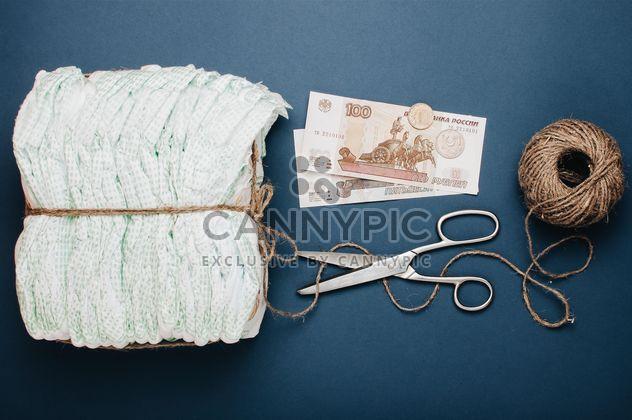 Pañales, madeja de hilo, tijeras y dinero en el fondo azul. Pañales por 3 dólares, Cheboksary, Rusia - image #342557 gratis