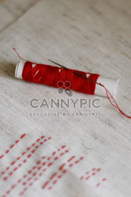 red bobbin thread with needle and stitches - Free image #342917