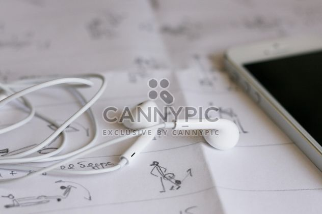 Closeup of smartphone and earphones on paper - Free image #345047