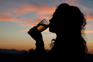 Silhouette of woman drinking beer at sunset - Kostenloses image #345057