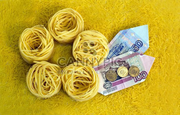 Italian tagliatelle nest and money on yellow background - бесплатный image #347947