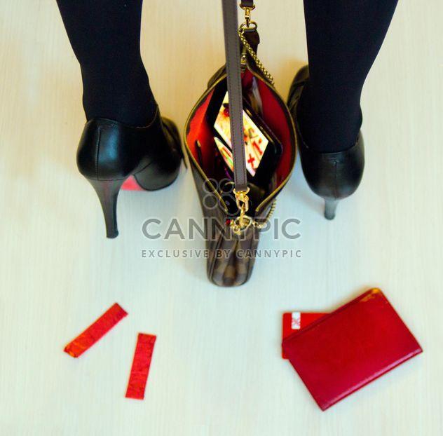 Pies femeninos en los zapatos de tacón alto con bolso negro - image #348007 gratis