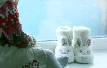 Child and cute slippers on windowsill - бесплатный image #348037