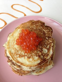 Pile of pancakes with caviar on pink plate - Free image #348387