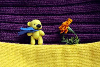 Toy yellow bear and marigold flower - бесплатный image #359167