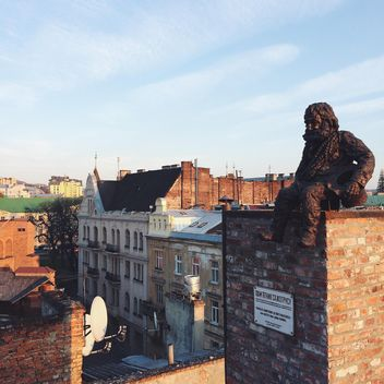 Chimneysweep monument is on the roof of a historic building House of Legends in Lviv, Ukraine - image #136237 gratis