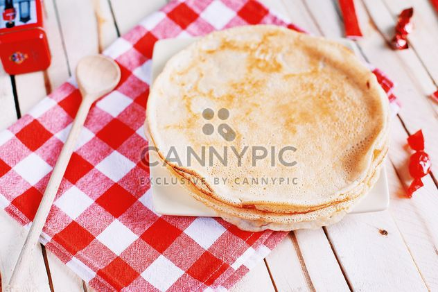 Pancakes and wooden spoon on checkered dishcloth - Free image #136447