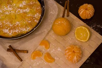 Charlotte with cinnamon and tangerines on table - бесплатный image #182597
