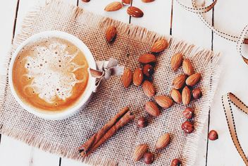 Cup of coffee, almonds, hazelnuts and cinnamon - image #183737 gratis