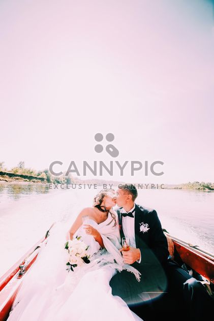 Happy wedding couple in boat on lake - image #184097 gratis