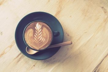 Coffee latte art on wooden table - бесплатный image #187077