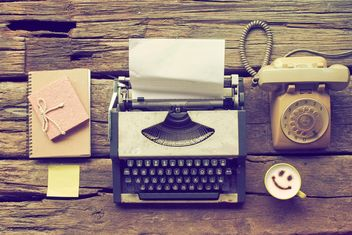 Vintage typewriter, phone, notebooks and cup of coffee on wooden background - image #187107 gratis