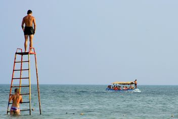 Guys on iron tower and tourists in boat - бесплатный image #187777