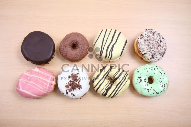 Donuts with different flavors on wooden background - Free image #187797