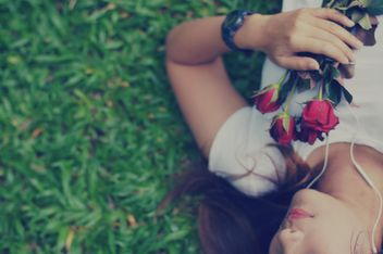 Girl with roses laying on grass - image #198087 gratis