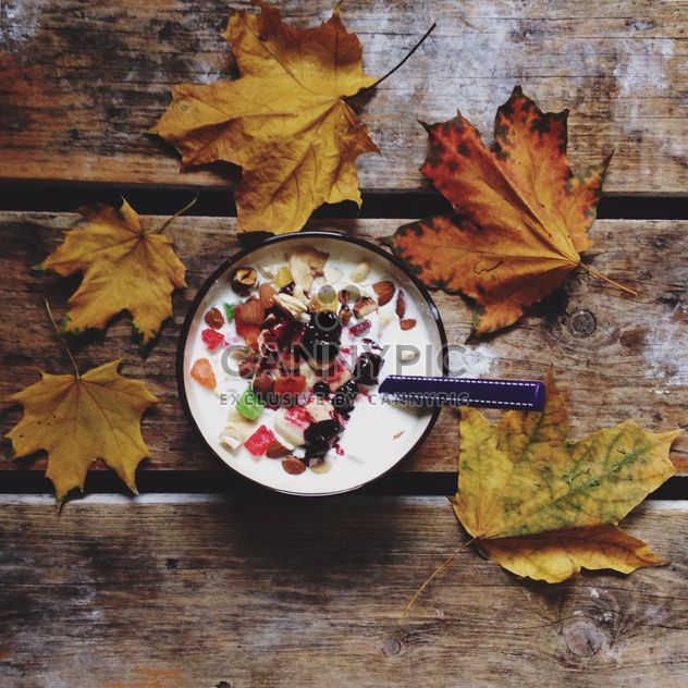 Muesli with dried fruit and nuts for breakfast and yellow leaves on wooden background - Free image #198377
