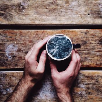 Male hands holding sea in the cup on wooden background - бесплатный image #198407