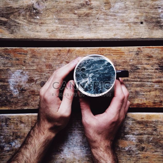 Male hands holding sea in the cup on wooden background - Free image #198407
