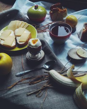 Soft-boiled egg, cheese sandwiches, fruit and tea for breakfast - image #272217 gratis