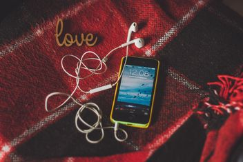Smartphone with earphones on checkered plaid - бесплатный image #273897